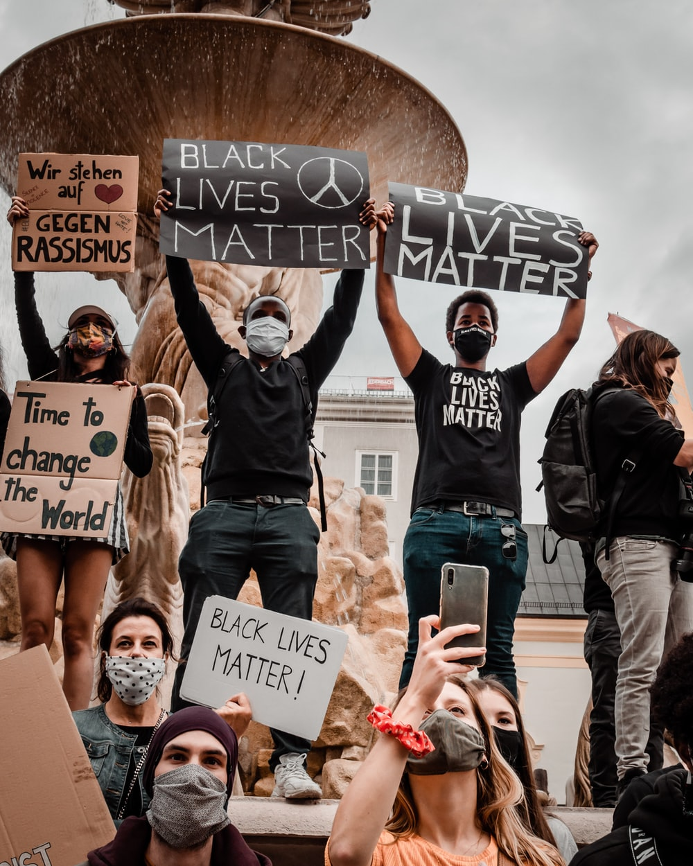 group of people holding white and black banner