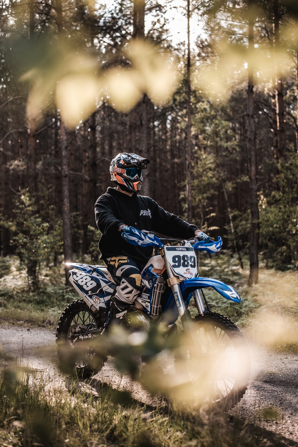 man in black and blue motorcycle suit riding blue and white motocross dirt bike