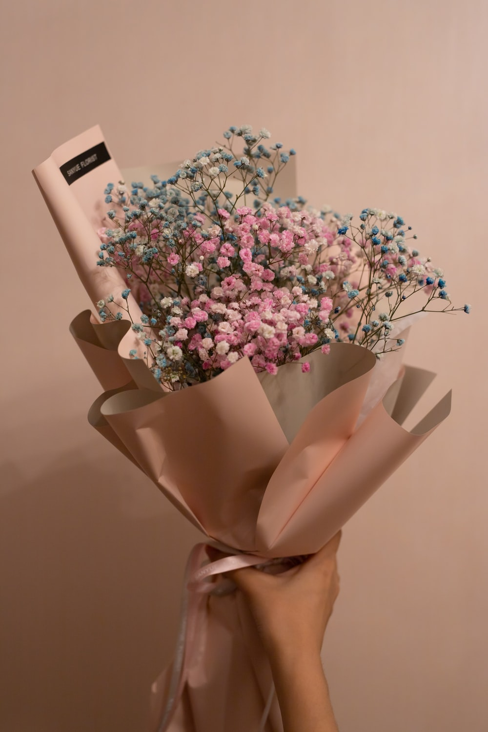 pink and white flowers in brown paper bag