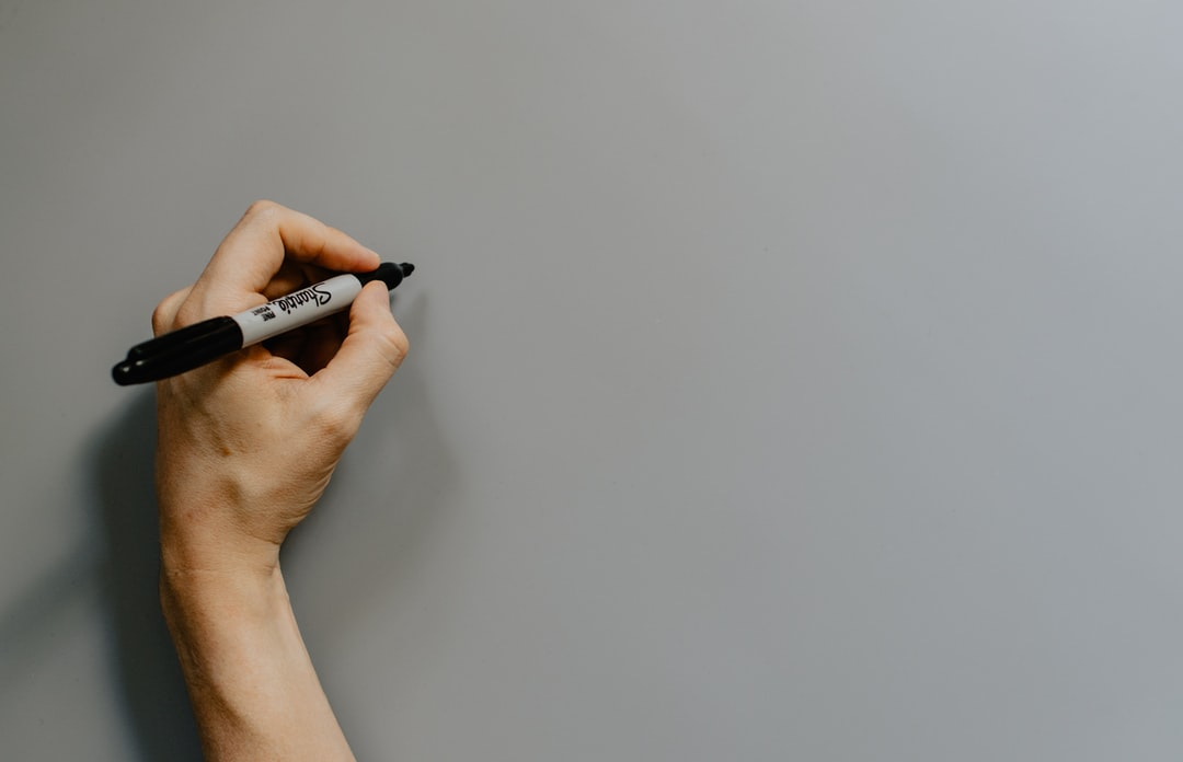 Hand holding a sharpie over a gray background