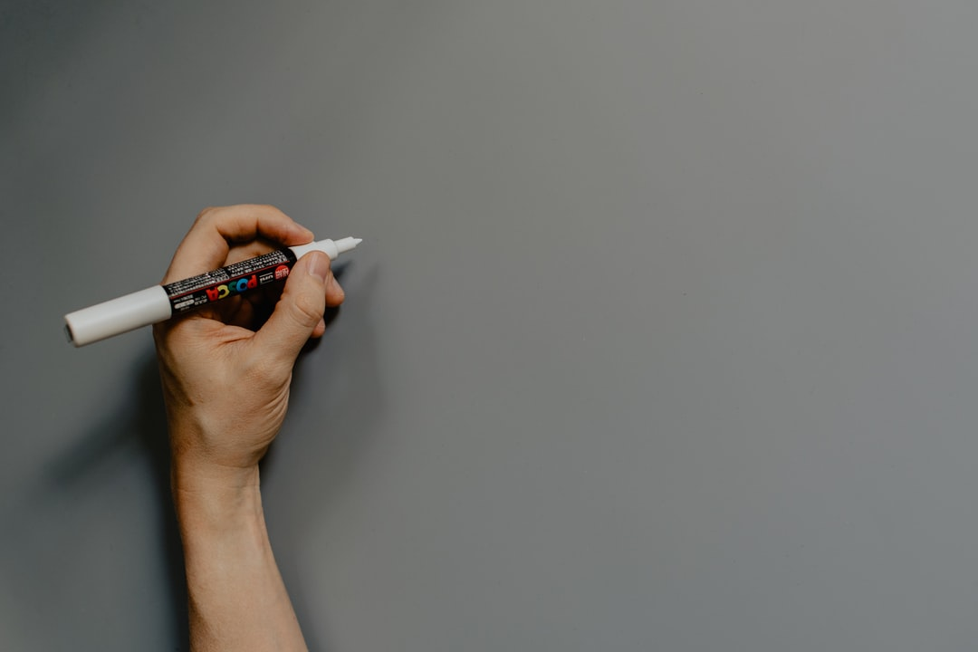 Hand holding a white Posca marker over a gray background