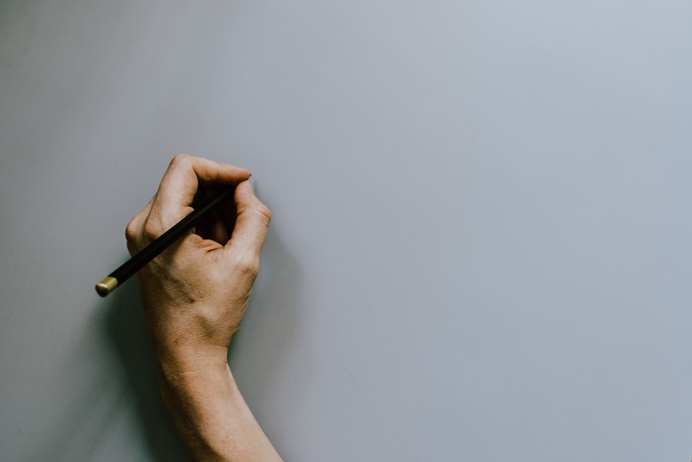 person holding black pen on white table
