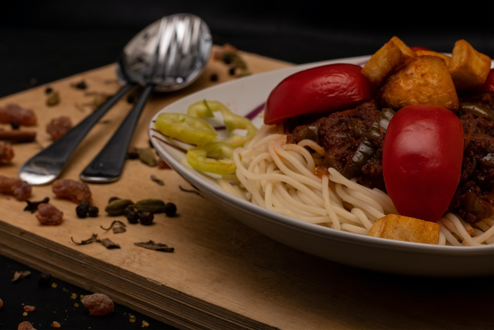 pasta on white ceramic plate beside red tomato on brown wooden table