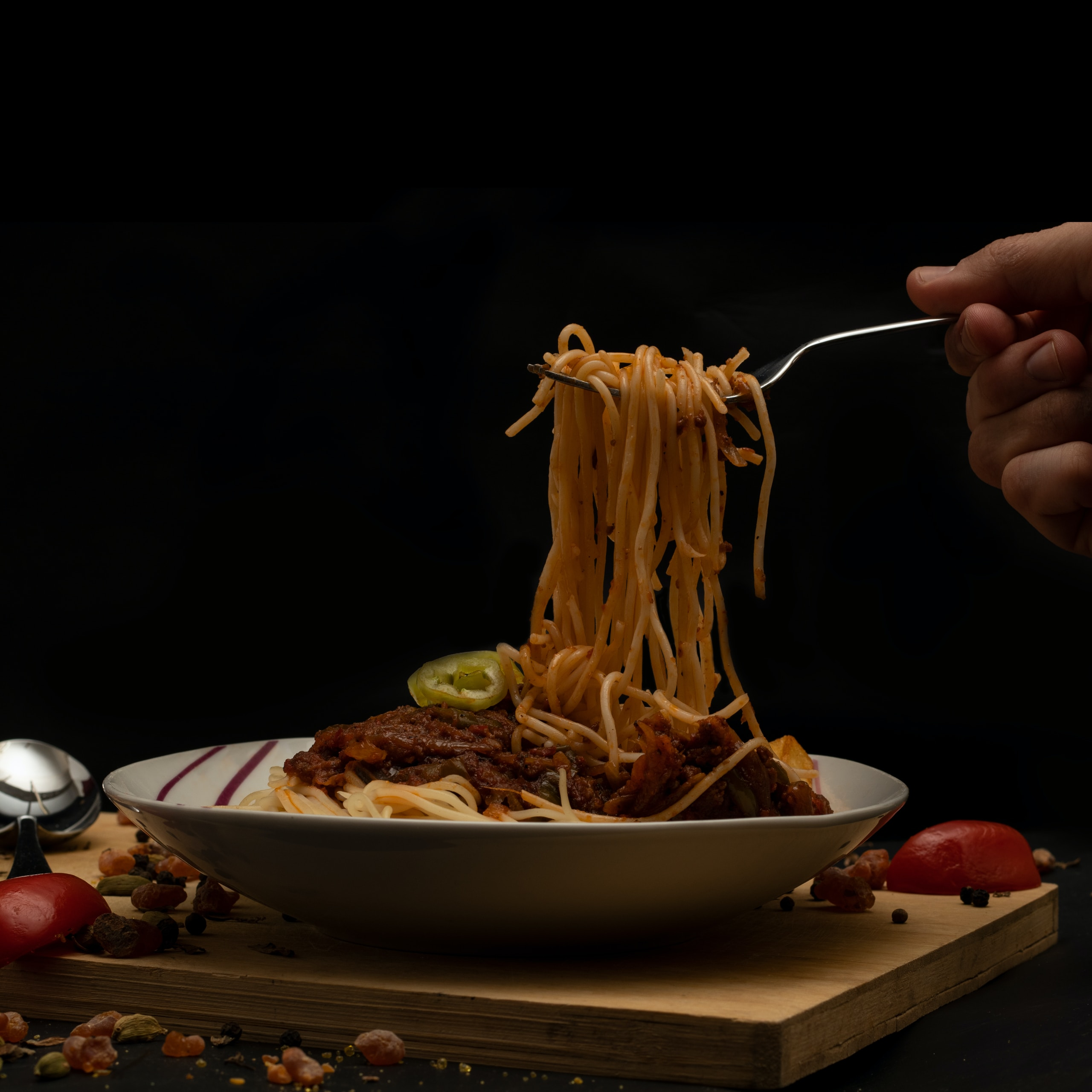 person holding stainless steel spoon and fork eating pasta