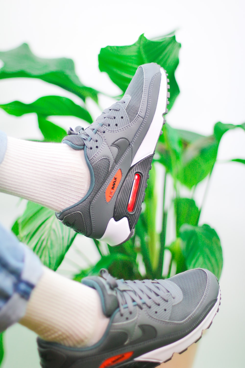 person wearing gray and white nike athletic shoes