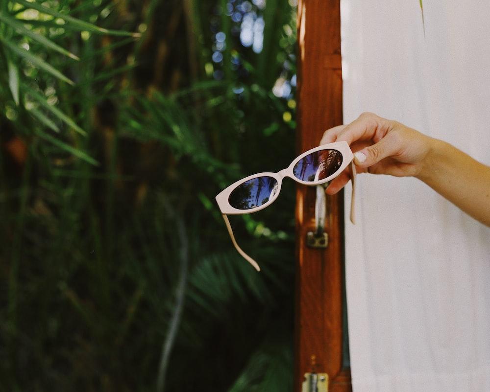 person holding white framed sunglasses
