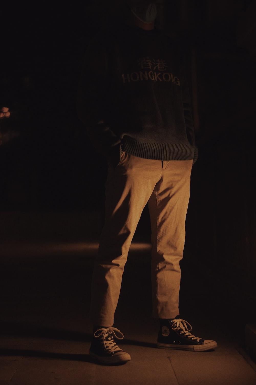 man in black jacket and brown pants
