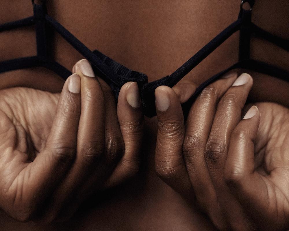 person holding black brassiere strap