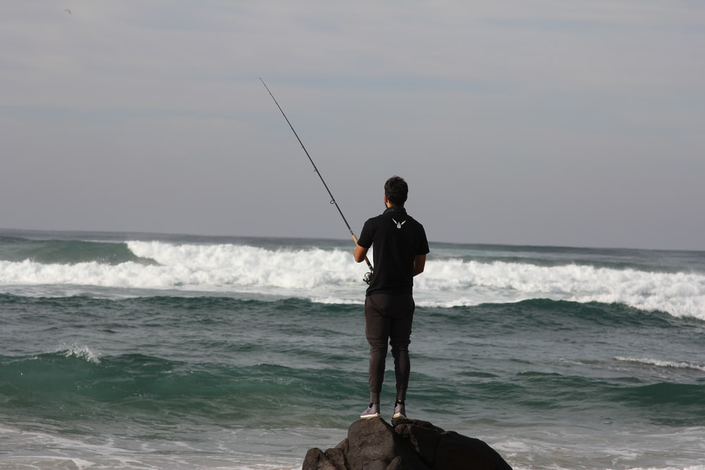 man in black jacket and black shorts holding fishing rod standing on brown rock near sea