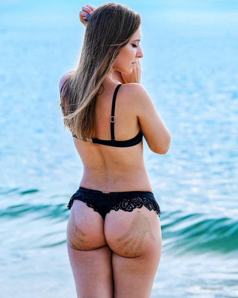woman in black bikini standing on sea shore during daytime