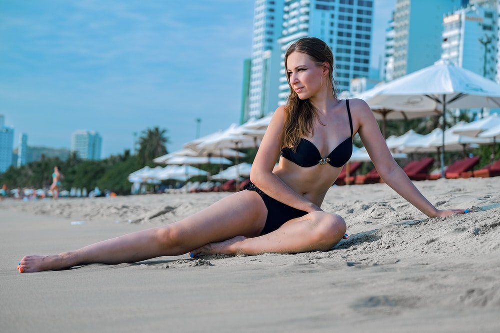 woman in black bikini lying on beach sand during daytime