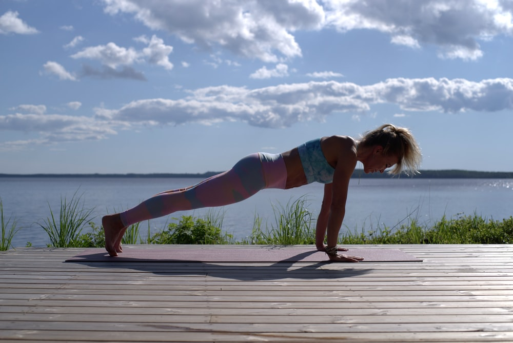 woman in blue sports bra and blue denim shorts standing on wooden dock during daytime