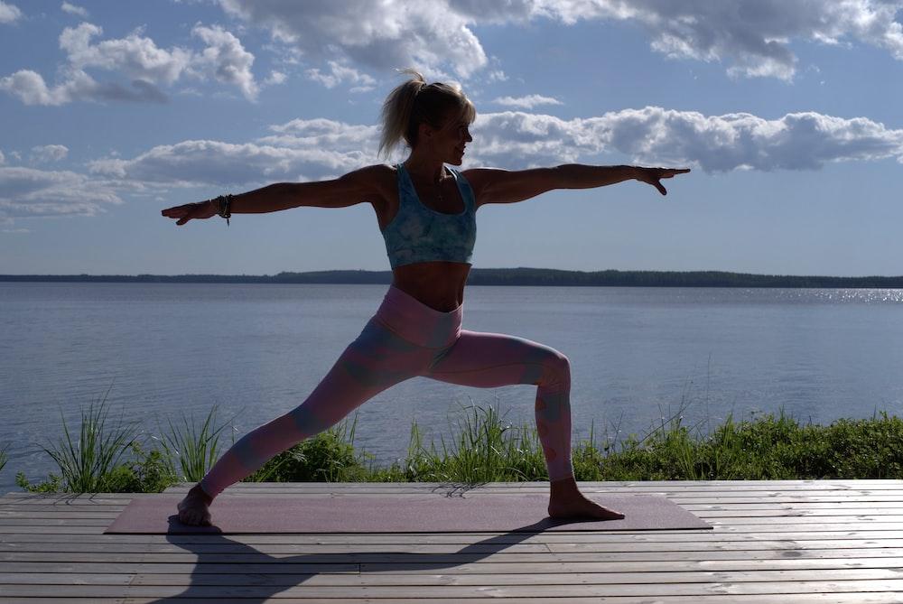 woman in blue bikini standing on dock during daytime