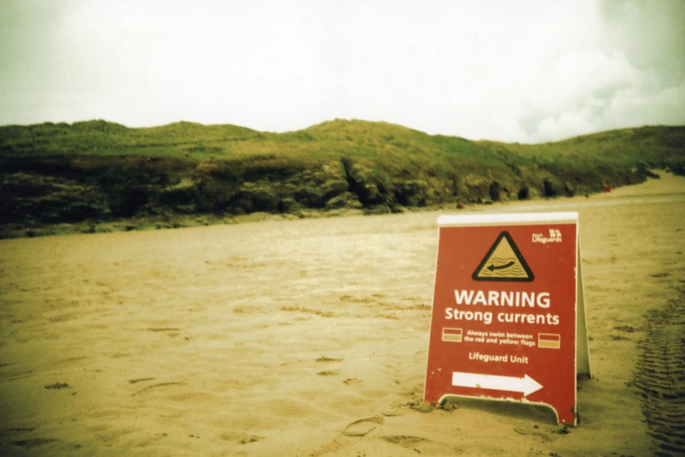 brown and white signage on brown sand during daytime