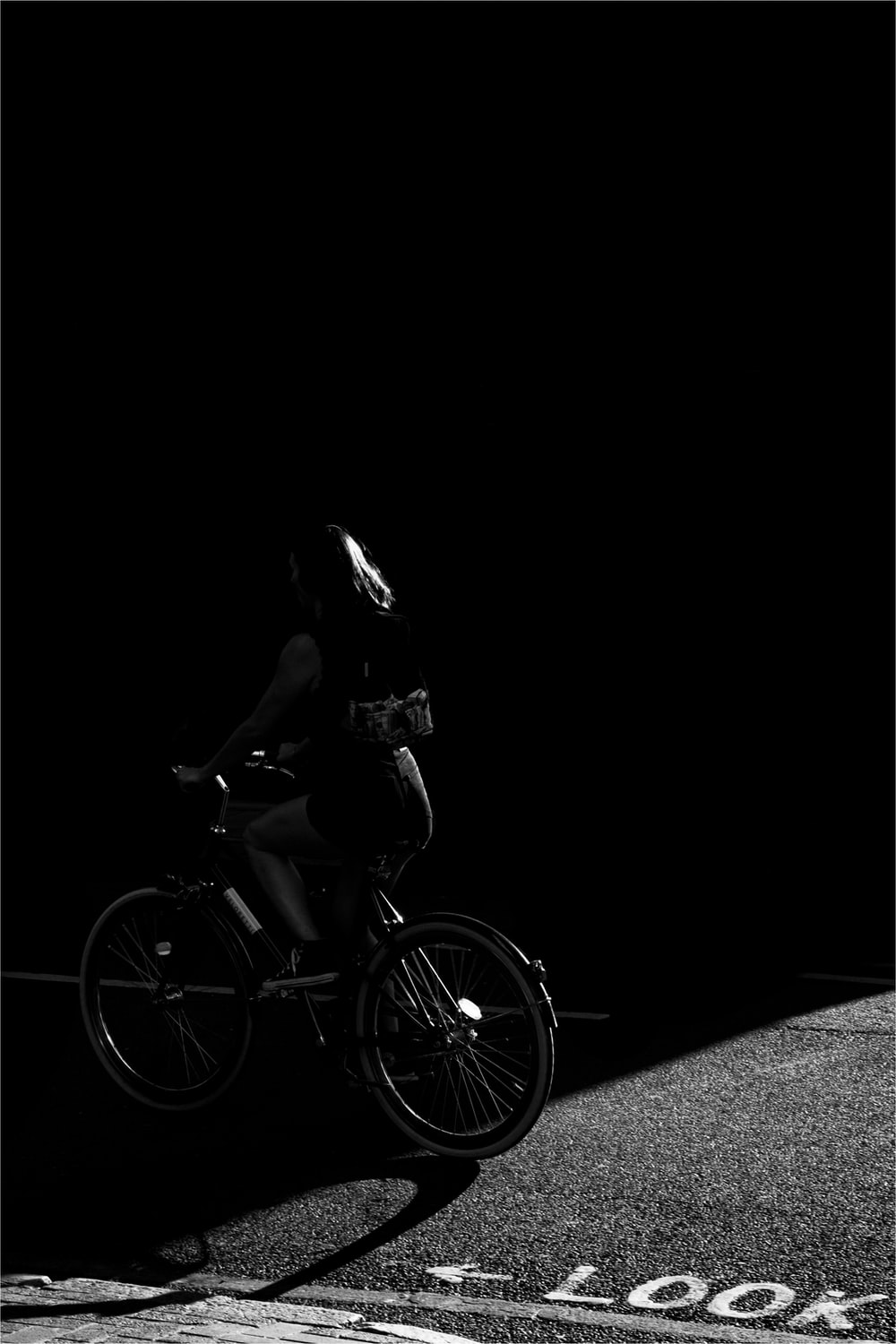 grayscale photo of woman riding bicycle