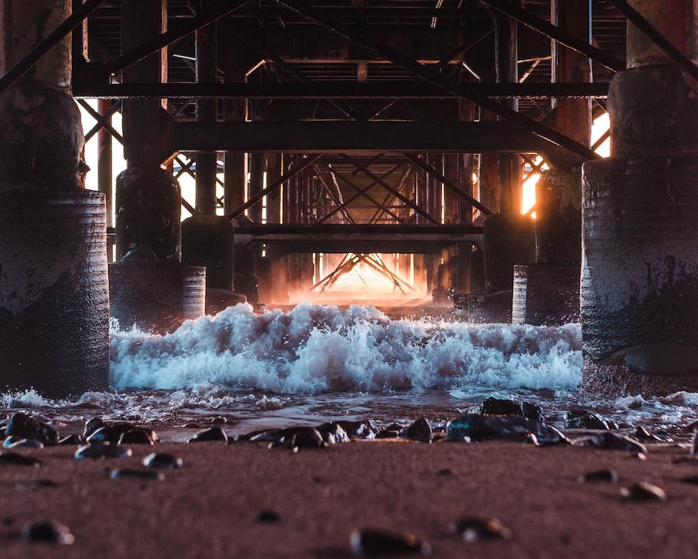 water falls under bridge during daytime