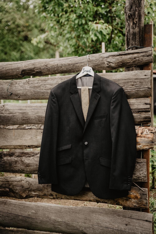 black suit jacket on white plastic clothes hanger