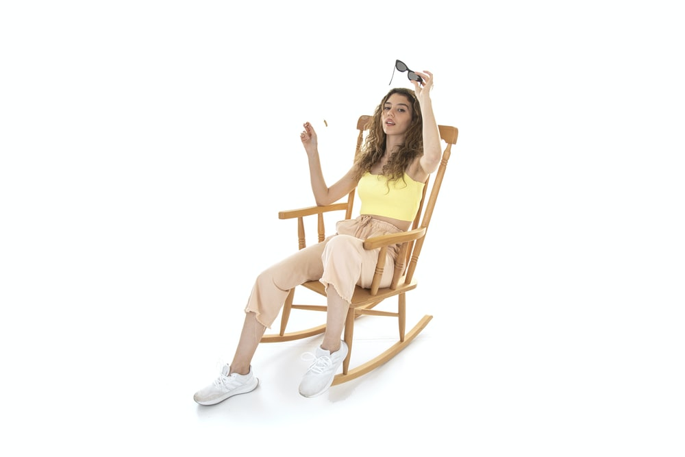 woman in black hat sitting on brown wooden rocking chair