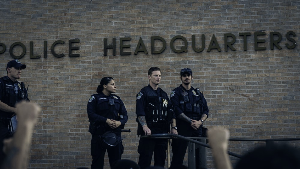 3 men in black uniform standing beside brown brick wall