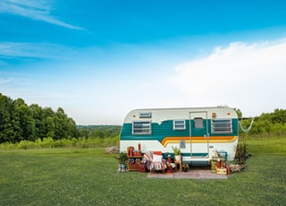 white and blue rv trailer on green grass field under blue sky during daytime