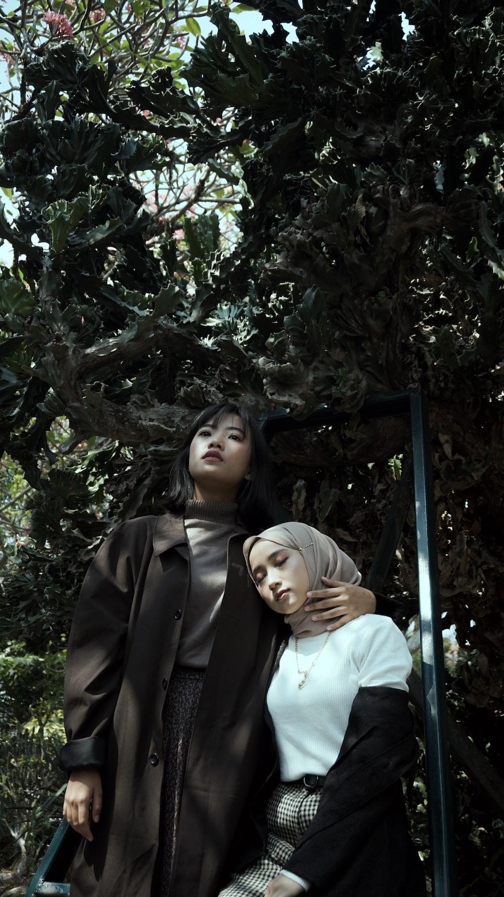 woman in black coat standing beside woman in white shirt