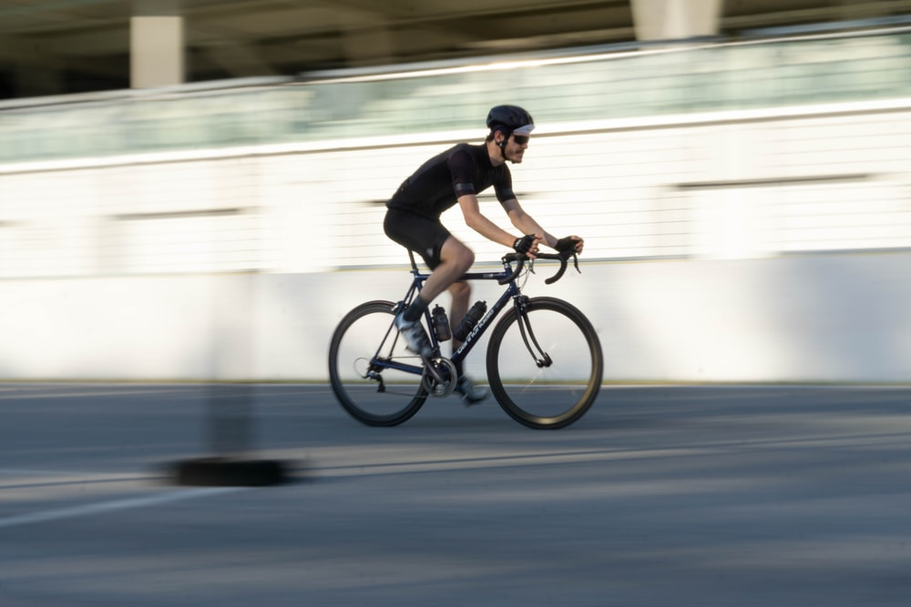 man in black shirt riding on bicycle