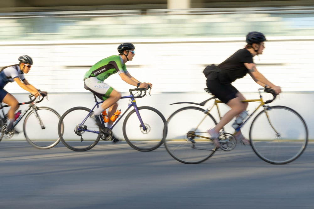 2 men riding on bicycle on road during daytime