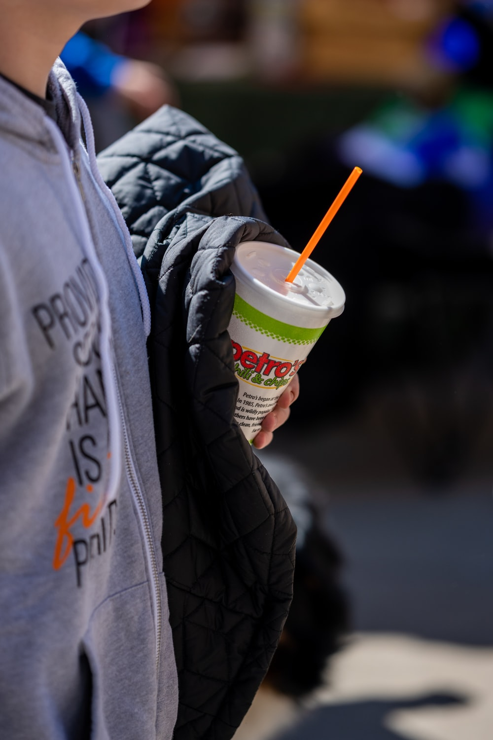 person holding white and green disposable cup with lid and straw