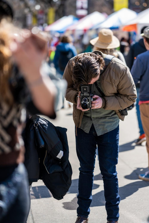 man in brown jacket and blue denim jeans holding black dslr camera