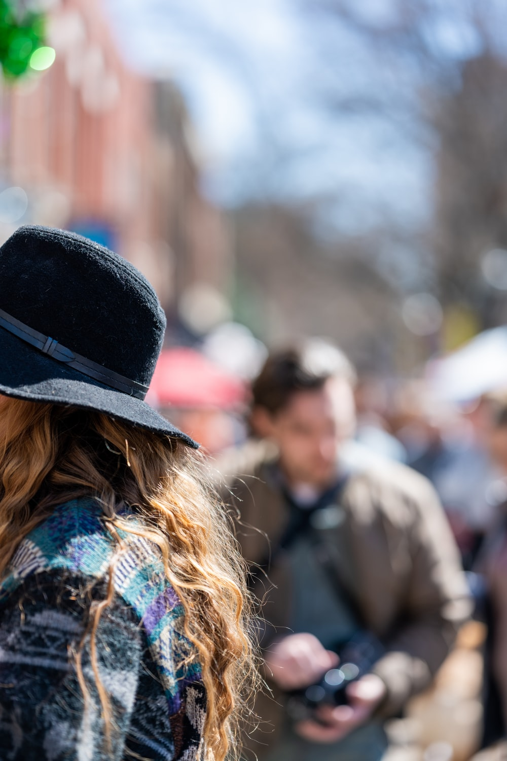 woman in black hat standing near people during daytime