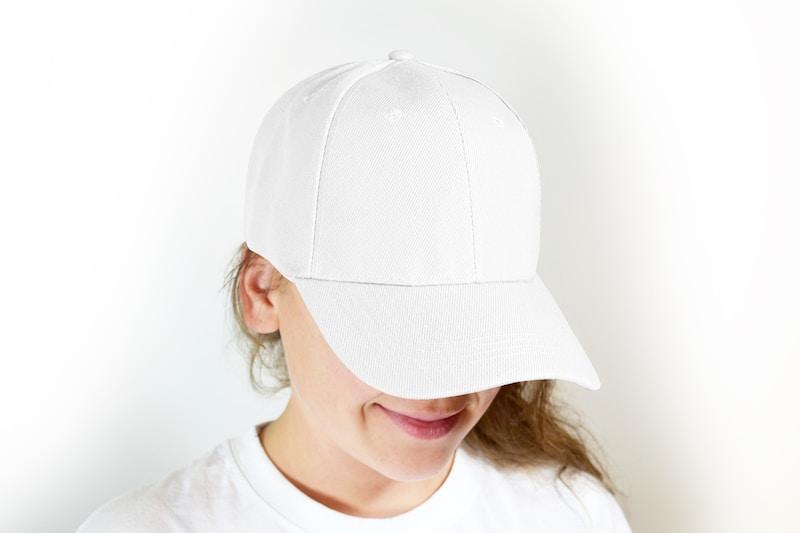 woman in white crew neck shirt wearing white cap