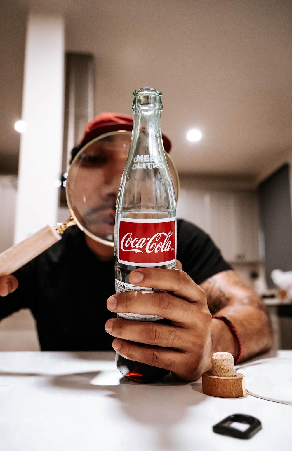 person holding coca cola glass bottle