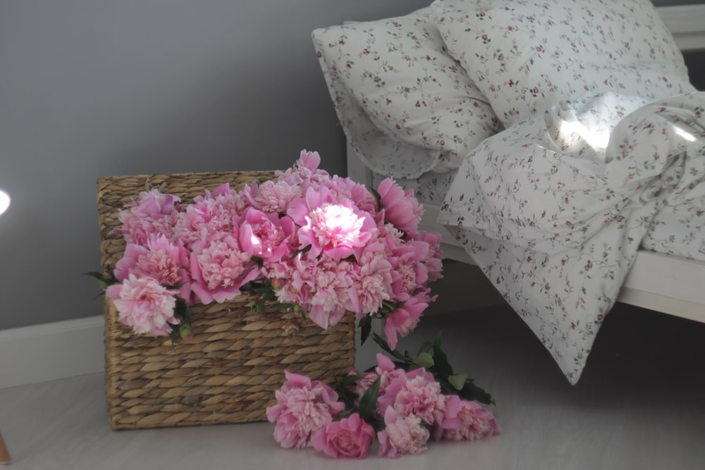 pink flowers on brown woven basket