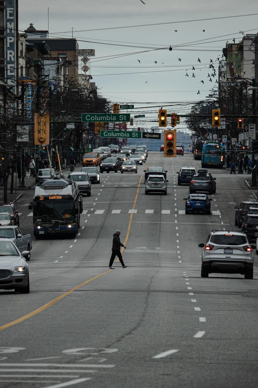 man in black jacket and pants walking on pedestrian lane during daytime