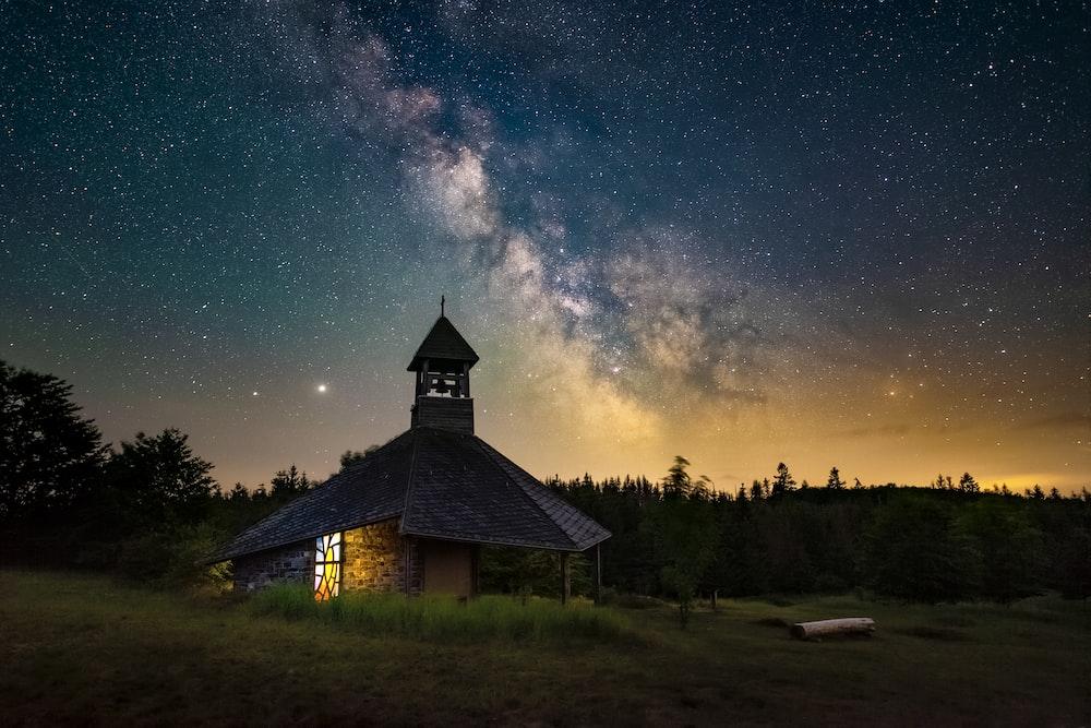brown wooden house under starry night