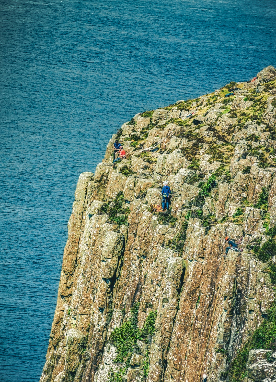 Rock climbers on the volcanic, hexagonal rock formations on the east face of Fair Head (Jun., 2020).