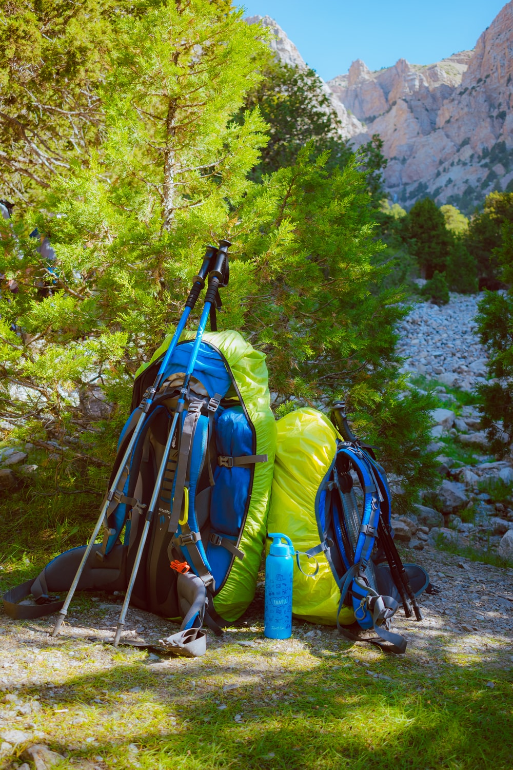 blue and black hiking backpacks on gray rocky ground