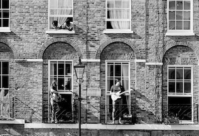 Islington grayscale photo of 2 women sitting on chair near brick building
