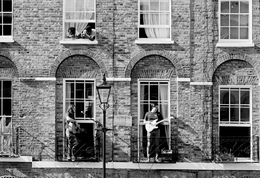 grayscale photo of 2 women sitting on chair near brick building