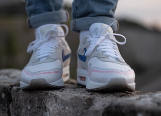 person in blue denim jeans wearing white and purple nike sneakers