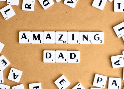 white and black letter blocks on brown surface father's day zoom background