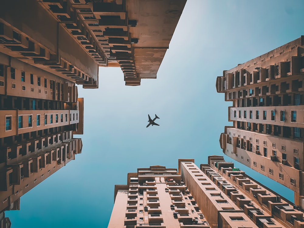 airplane flying over high rise buildings during daytime