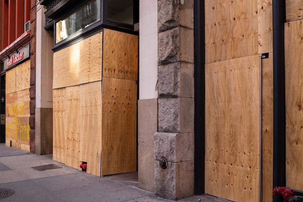 brown wooden door near gray concrete wall
