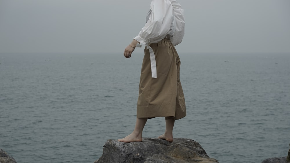woman in white hijab and brown dress standing on rock near body of water during daytime