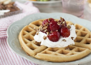 waffle with red and white cream on white ceramic plate