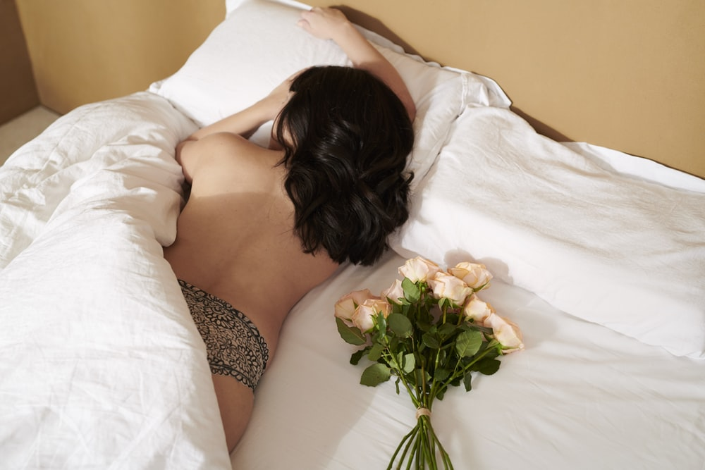 woman in black and white floral bikini lying on bed