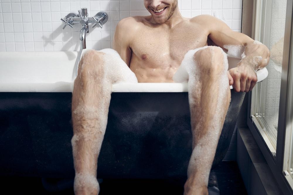 topless man sitting on bathtub