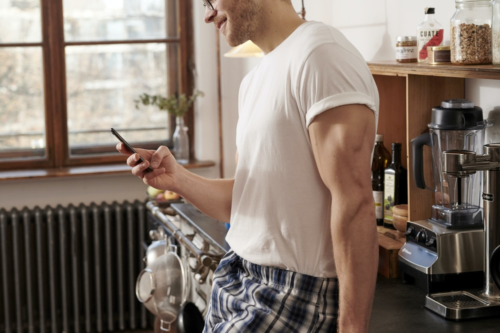 man in white crew neck t-shirt and blue and white plaid shorts holding smartphone