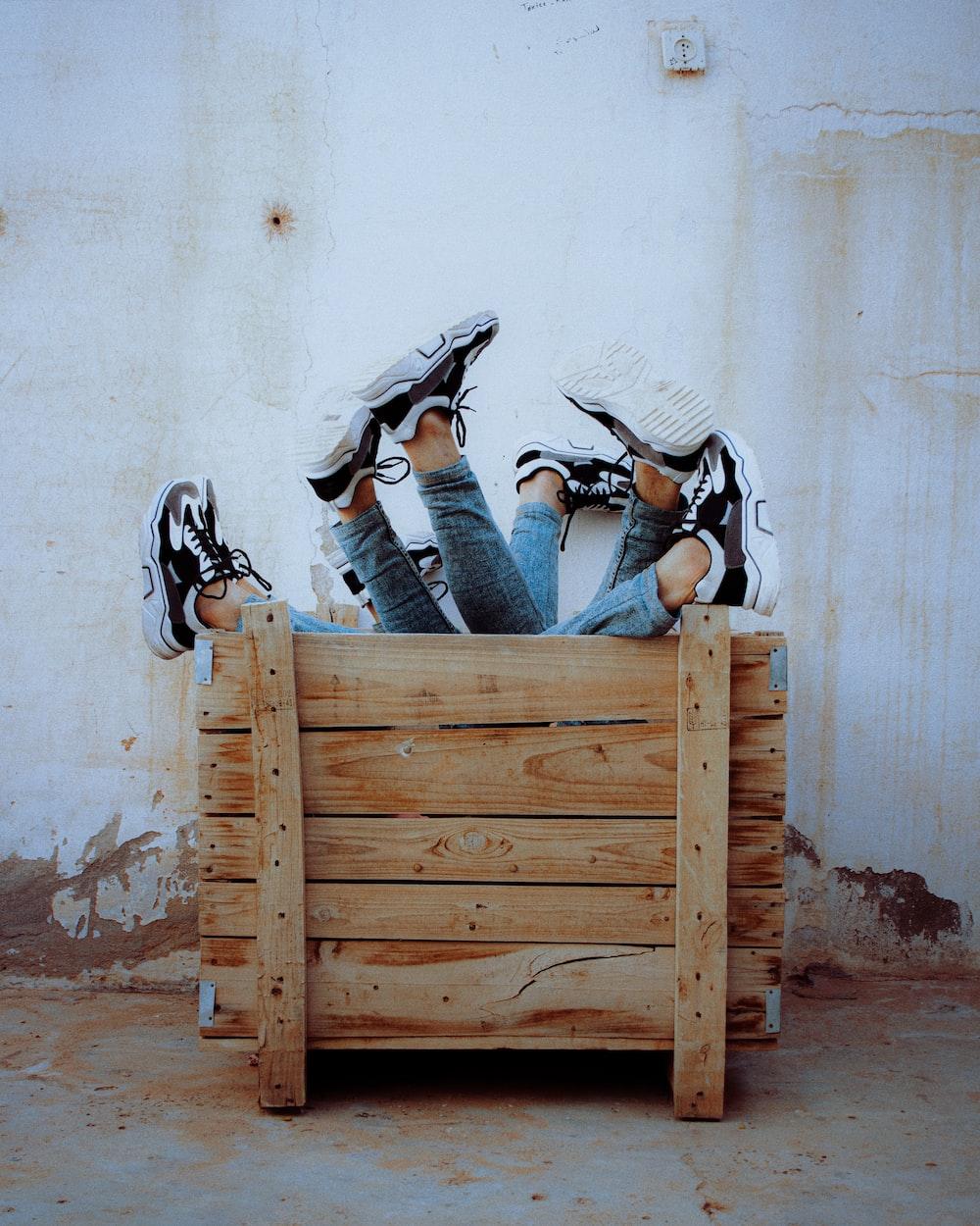 man in blue denim jeans sitting on brown wooden bench