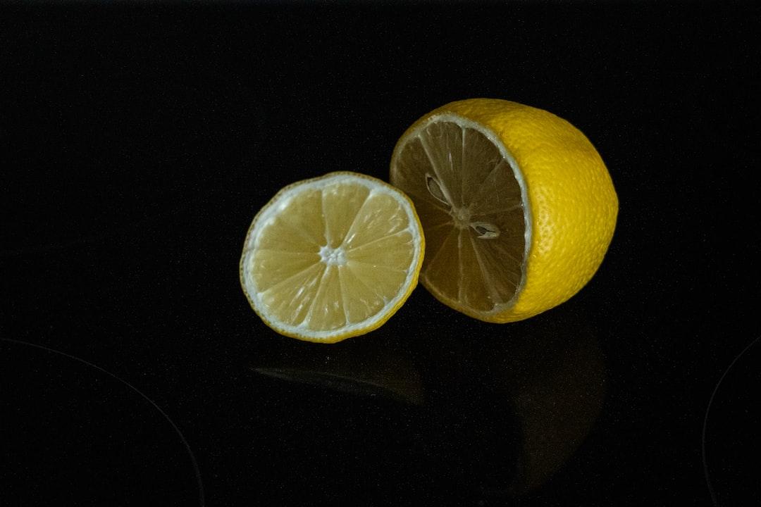 A lemon, cut and against a black background.